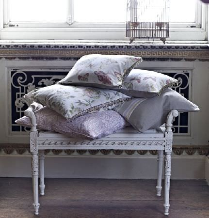 Prestigious Textiles -  Langdale Fabric Collection - An ornately carved white wood stool heaped with five pale grey and white floral, striped and patterned scatter cushions
