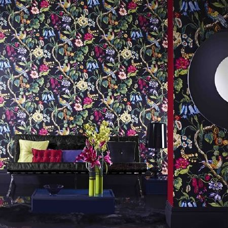Prestigious Textiles -  Life Fabric Collection - Busy multicoloured floral wallpaper with a black background, black leather effect sofa, coloured cushions, navy table and lime green vases