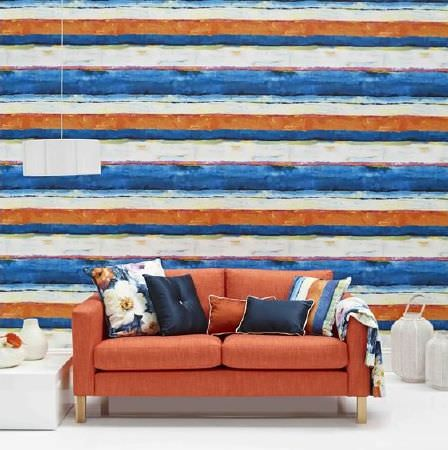 Prestigious Textiles -  Life Fabric Collection - Seaside feel orange, blue and cream striped wallpaper, orange sofa with blue, orange and cream cushions, white lampshade, table and vases