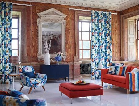 Prestigious Textiles -  Life Fabric Collection - Bright blue floral patterned curtains, armchairs and cushions, orange sofa, red square seat, large framed mirror, side table and white vase