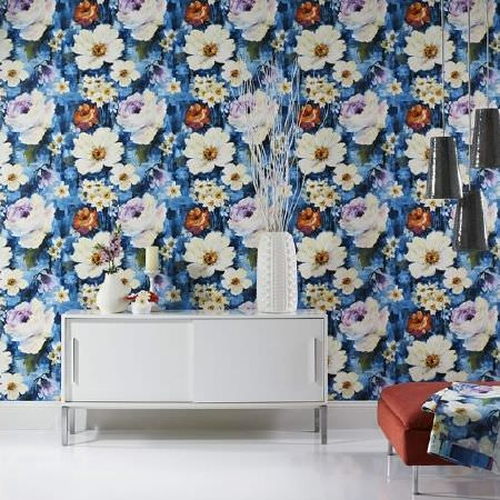 Prestigious Textiles -  Life Fabric Collection - White side unit with sliding doors, a large white vase, blue and cream floral wallpaper, a hanging black light and burnt orange footstool
