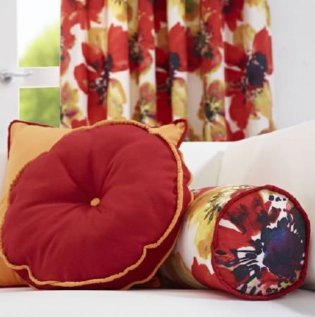 Prestigious Textiles -  Life Fabric Collection - Round red cushion with orange piping, inversely coloured square cushion, coordinating floral bolster cushion and matching curtains