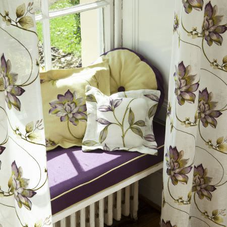Prestigious Textiles -  Madame Fabric Collection - Purple seating pad with green edges, green and white cushions with purple flowers, and a white curtain with a detailed purple flower print