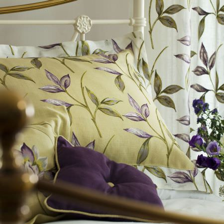 Prestigious Textiles -  Madame Fabric Collection - Light green cushion with dark green and purple leaf images, a dark purple cushion, and a white curtain with green leaf decoration