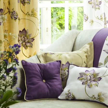 Prestigious Textiles -  Madame Fabric Collection - Yellow curtain with detailed stitching of flowers in purple, a purple pillow, and a green and white cushions with flowers on a white couch