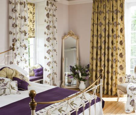 Prestigious Textiles -  Madame Fabric Collection - An antique metal bed with white and purple bedding with flowers, and white and yellow curtains with purple and green flower stitchings