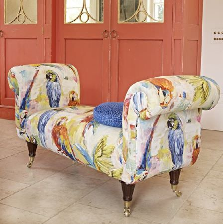 Prestigious Textiles -  Mardi Gras Fabric Collection - A blue cushion on a bench seat with large armrests, covered with multicoloured watercolour effect parrot print fabric