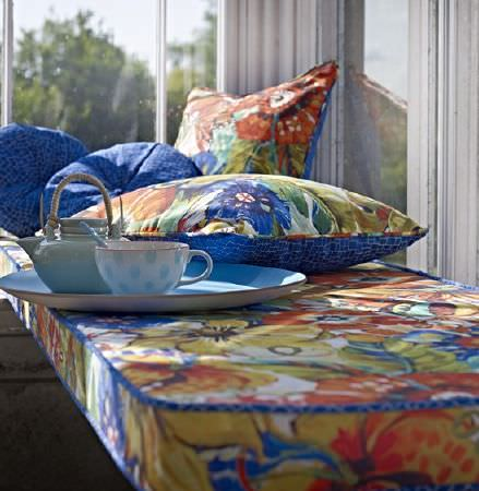 Prestigious Textiles -  Mardi Gras Fabric Collection - A bench seat cushion and 4 double sided scatter cushions, covered with patterned blue fabric and large red and orange florals