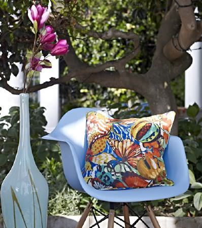 Prestigious Textiles -  Mardi Gras Fabric Collection - A tall white vase beside a modern light blue moulded plastic chair with wooden legs, and an orange and blue floral cushion