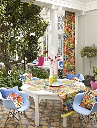 Prestigious Textiles -  Mardi Gras Fabric Collection - A patio table with 4 light blue moulded plastic chairs, an orange, blue and green floral table runner, curtain and cushions