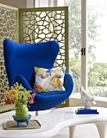 Prestigious Textiles -  Mardi Gras Fabric Collection - A Royal blue armchair, a parrot print cushion, a curving bright white coffee table, and a screen with abstract cut outs