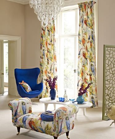Prestigious Textiles -  Mardi Gras Fabric Collection - Multicoloured parrot print fabric on curtains, a cushion and a padded bench seat, with a white table and a blue armchair