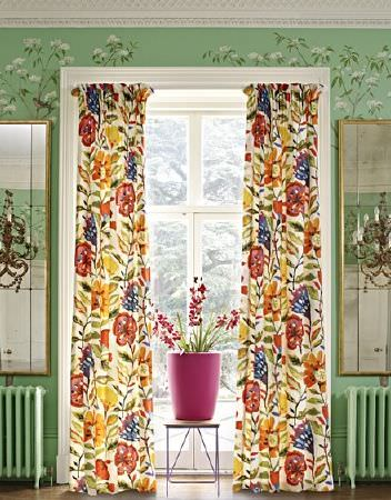 Prestigious Textiles -  Mardi Gras Fabric Collection - Large French doors with white, red and orange curtains featuring a large floral print, with a large hot pink flowerpot