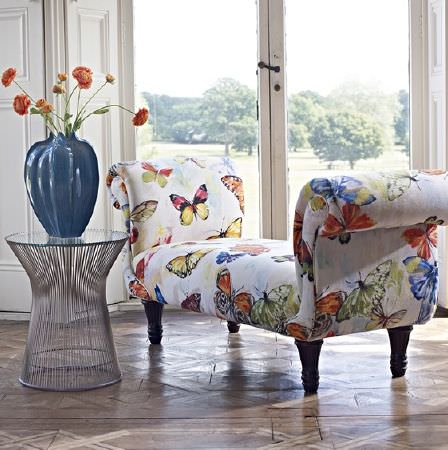 Prestigious Textiles -  Mardi Gras Fabric Collection - A silver wire table, a large blue vase, and a padded bench seat covered with white, blue and orange butterfly print fabric
