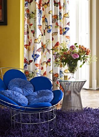Prestigious Textiles -  Mardi Gras Fabric Collection - A wire tub style chair with bright blue cushions, with a wire table, a fluffy indigo rug and butterfly print curtains