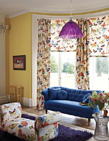 Prestigious Textiles -  Mardi Gras Fabric Collection - A Royal blue sofa, a fluffy indigo rug, and multicoloured butterfly print fabric covering a padded bench seat and curtains