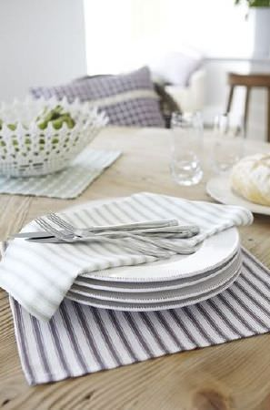 Prestigious Textiles -  Marina Fabric Collection - White plates on square place mats in blue and white stripes and green and white checks, with cutlery and a white cut-out fruit bowl