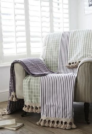 Prestigious Textiles -  Marina Fabric Collection - Wooden-legged armchair in neutral stripes with fabrics edged with tassels in purple/white checks and stripes, green/white checks and stripes