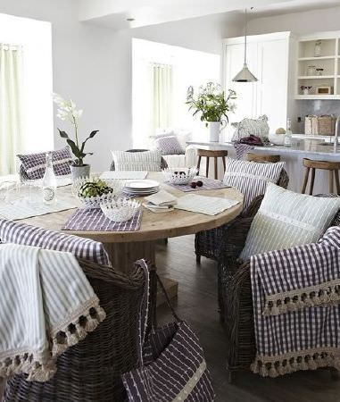Prestigious Textiles -  Marina Fabric Collection - Solid wood table, wicker chairs, tablecloths, cushions, bags all made in purple/green and white stripes or checks, white bowls, wood stools