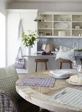 Prestigious Textiles -  Marina Fabric Collection - White plates and checked tablecloths on a round wood table, checked cushions on a woven chair and wood stool, shopping bags and a jug vase