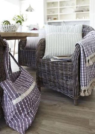 Prestigious Textiles -  Marina Fabric Collection - Purple striped shopping bag with button detail, with woven wicker style chairs, wood table, checked fabric, and a green and white cushion