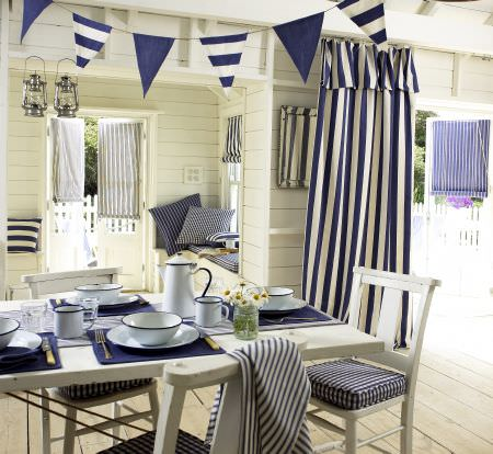 Prestigious Textiles -  Maritime Fabric Collection - Blue and white striped roman blinds and curtains, plaid seating pads, blue placemat, and bunting