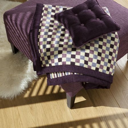 Prestigious Textiles -  Medici Fabric Collection - Dark purple upholstered footstool with a purple chequered blanket with purple edges, and a plain purple cushion for a classic house