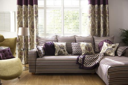 Prestigious Textiles -  Medici Fabric Collection - A purple, blue and white striped upholstered couch with round and square cushions, and a chequered quilt, in front of a classic curtain