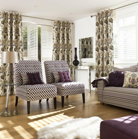 Prestigious Textiles -  Medici Fabric Collection - Purple and white chequered chair upholstery with striped and plain purple cushions, with curtains with a classic leaf and flower design