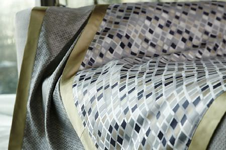 Prestigious Textiles -  Metropolis Fabric Collection - Satin effect fabric with grey, black and silver squares, and another silver satin effect fabric with overlapping squares, both edged in green