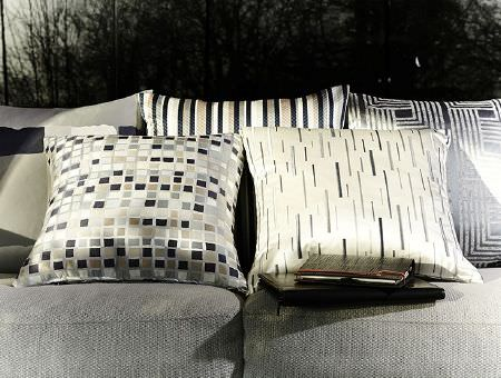 Prestigious Textiles -  Metropolis Fabric Collection - Cushions in shades of grey, cream and black, featuring square designs, stripes and geometric cushions, laid out on a grey sofa