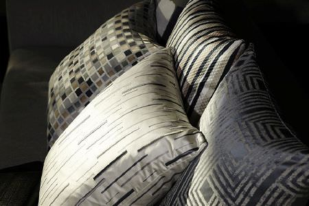 Prestigious Textiles -  Metropolis Fabric Collection - Grey sofa with grey and cream cushions; cream with dashed stripes, geometric print, plain stripes, and small, mosaic style squares