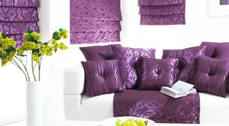 Prestigious Textiles -  Mexicana Fabric Collection - Striking purple and white lounge area showing purple cushions, Roman Blinds and throw with leaf and patterned motifs