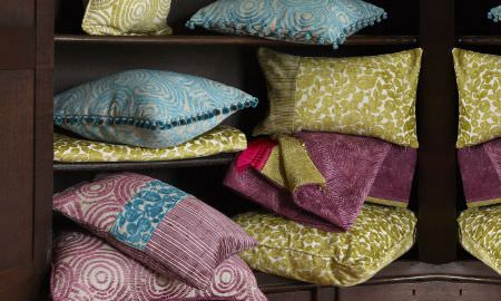 Prestigious Textiles -  Mezzo Fabric Collection - Assortment of Mezzo Collection velvet cushions with circular and striped patterns, in greens, purples and blues