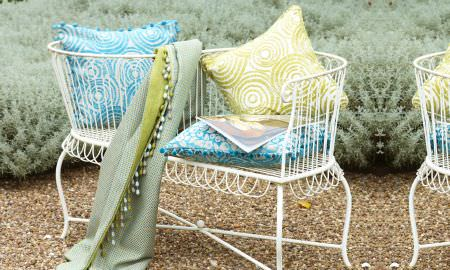 Prestigious Textiles -  Mezzo Fabric Collection - outdoor seating area with Mezzo colelction blue and green velvet cushions, and matching green tasselled throw