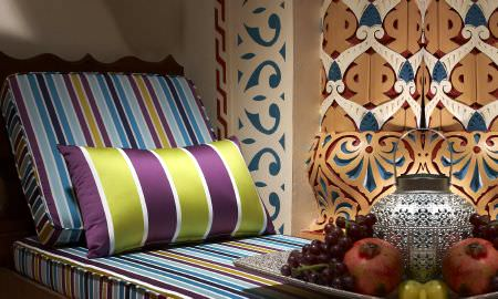 Prestigious Textiles -  Monte Carlo Fabric Collection - Green adn purple striped cushion and blue and brown striped daybed mattress and cushion
