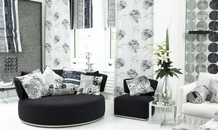 Prestigious Textiles -  Multi Media Fabric Collection - Modern room setting with a round upholstered couch and a small upholstered chair with white cushions, and a modern white curtain
