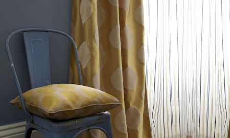 Prestigious Textiles -  Nouveau Fabric Collection - Grey window seat with plush golden cushion in geometric design, matching curtains