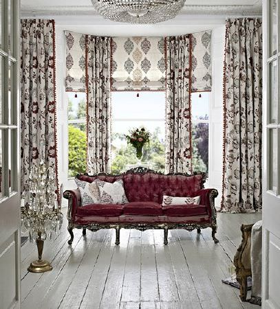 Prestigious Textiles -  Opera Fabric Collection - Maroon, grey and cream patterned cushions, curtains and blinds with an opulent dark red sofa with a dark grey wood frame