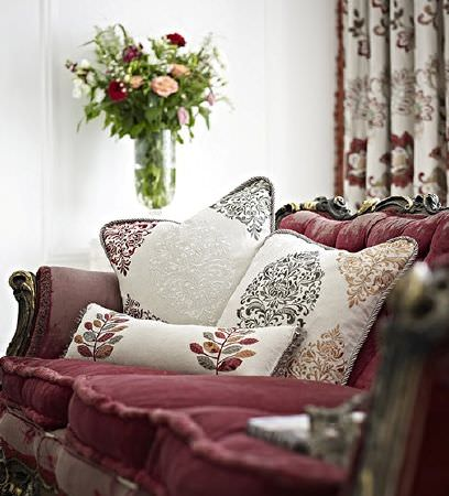 Prestigious Textiles -  Opera Fabric Collection - Large sofa with an ornate wood frame and dark red seatss, with patterned cushions and curtains in red, grey, gold and cream