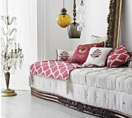 Prestigious Textiles -  Opera Fabric Collection - Large white sofa bed with a wooden base, red and white patterned throws and cushions, a large gold frame and chandeliers
