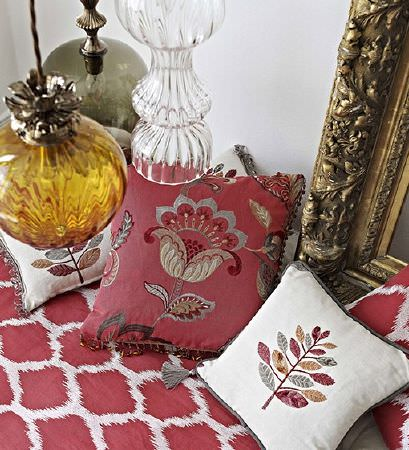 Prestigious Textiles -  Opera Fabric Collection - White and dark red cushions with floral and leaf designs, a matching throw, an ornate gold mirror and hanging glass lights