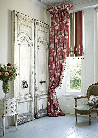 Prestigious Textiles -  Opera Fabric Collection - Long dark red and light grey patterned fringed curtains, a striped blind, a green and gold armchair and a white table