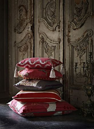 Prestigious Textiles -  Opera Fabric Collection - A stack of five luxurious deep red, grey and off-white cushions with different patterns, one with grey-white tassels