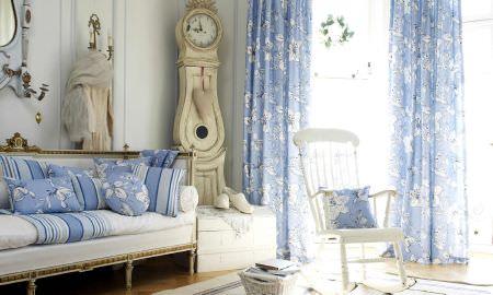 Prestigious Textiles -  Orient Fabric Collection - Crisp cream sofa with light blue and white striped throw and floral design cushions and curtains