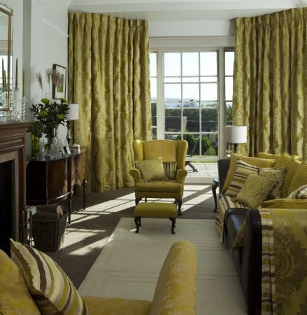 Prestigious Textiles -  Overture Fabric Collection - Pinched lime green curtains with a large floral pattern, an antique upholstered easy chair and footstool, a black couch with bright cushions