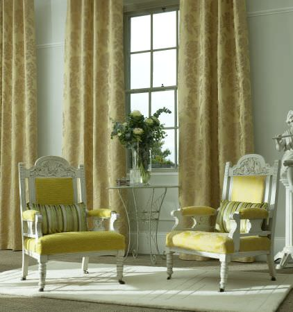 Prestigious Textiles -  Overture Fabric Collection - Antique chairs with bright green upholstery, padding and green striped cushions, in front of lime green curtains with a large flower pattern