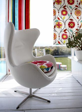 Prestigious Textiles -  Palm Beach Fabric Collection - Modern house with colourful striped curtain and a white curtain with a modern flower design, a white leather easy chair and a round cushion
