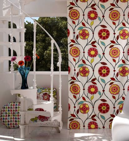 Prestigious Textiles -  Palm Beach Fabric Collection - A white curtain with a modern abstract flowers and vines, a round colourful cushion, and a large seating pad with a modern flower design