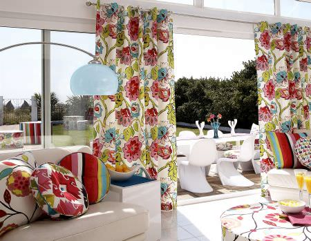 Prestigious Textiles -  Palm Beach Fabric Collection - Big modern flowery curtains in pink, blue and green, a white upholstered couch with round colourful cushions and an upholstered stool